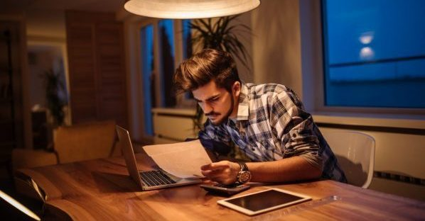 Een man bekijkt papieren terwijl hij op zijn laptop een aanvraag indient