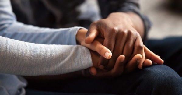 Twee mensen zoeken troost door elkaars handen vast te houden