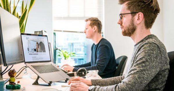 Twee medewerkers aan het werk, een van hen bekijkt de Schadefonds-website