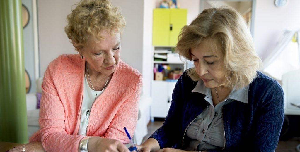 Een medewerker helpt een vrouw bij het indienen van een aanvraag