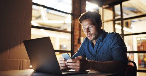 Een man kijkt op zijn smartphone en laptop